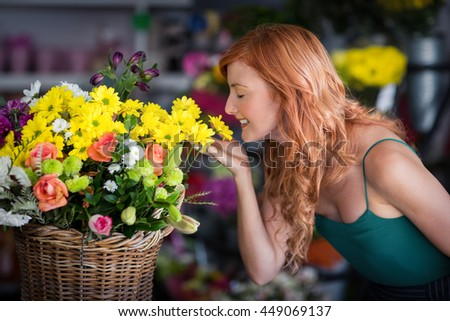 Smiling female florist smelling flowers at flower shop - stock photo