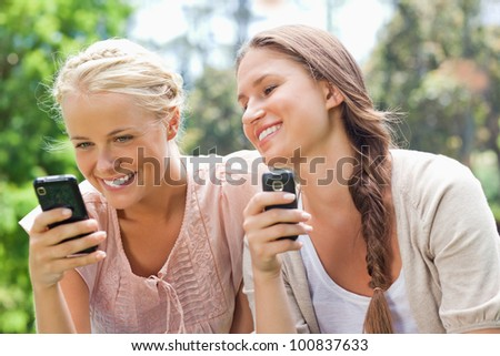 Smiling female friends with cellphones - stock photo