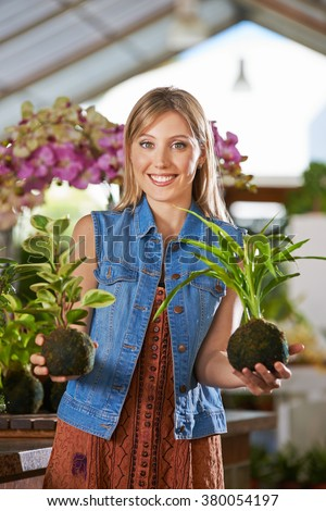 Smiling female gardener holding two kokedama in nursery in her hands - stock photo