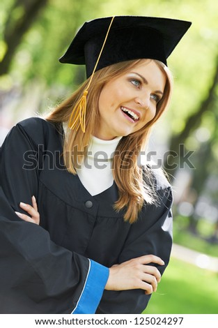smiling female graduate student girl in the park cheerful and happy - stock photo