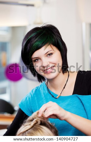 smiling female hairdresser at work in salon - stock photo