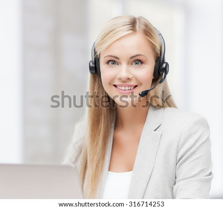 smiling female helpline operator with headphones and laptop - stock photo