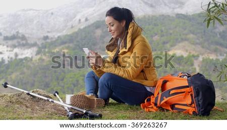 Smiling female hiker using her phone - stock photo