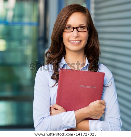 Smiling female holding a book against the blurred background - stock photo