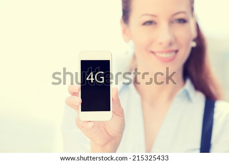 Smiling female holding mobile smart phone with 4G sign on screen isolated outside city background focus on smartphone. New gadget technology, connection concept. Positive human emotion face expression - stock photo