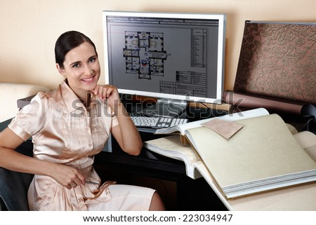 Smiling female interior designer at her workplace - stock photo