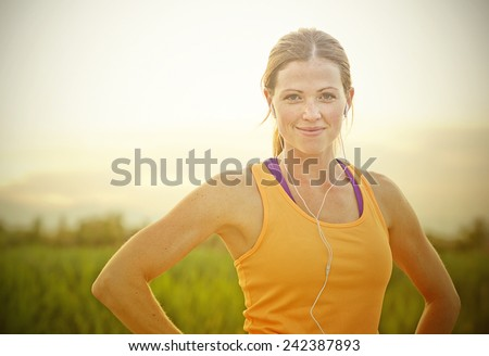 Smiling Female Jogger at Sunset (intentional sun glare) - stock photo