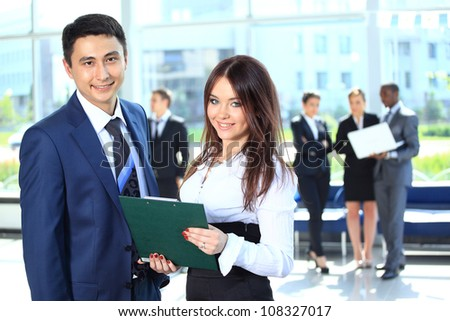 Smiling female leader discussing business plan with confident colleagues - stock photo