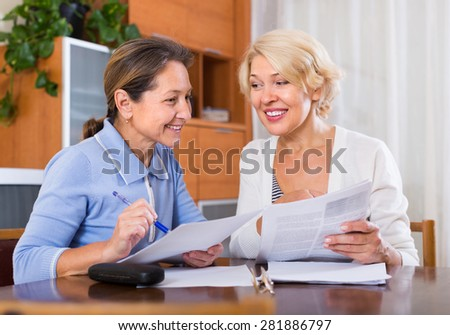 Smiling female pensioners working with documents at the table. Focus on brunette - stock photo