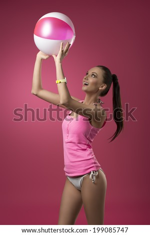 smiling female playing with beach ball in summertime and wearing pink singlet on bikini, perfect body.  - stock photo