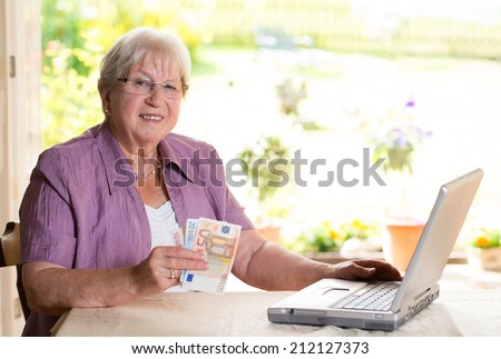 smiling female senior with money is using computer - stock photo