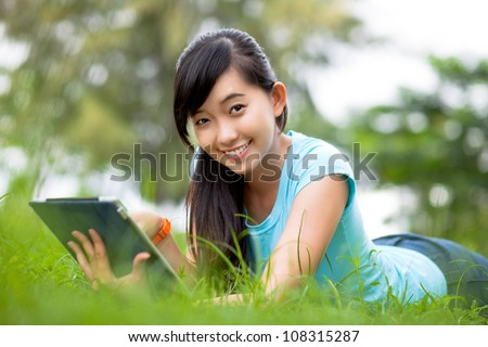 Smiling female student lying on grass with digital tablet and looking at camera - stock photo