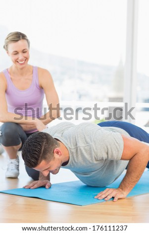 Smiling female trainer assisting man with push ups at gym - stock photo