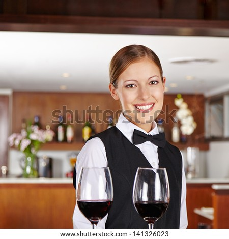 Smiling female waiter serving glasses of red wine in restaurant - stock photo
