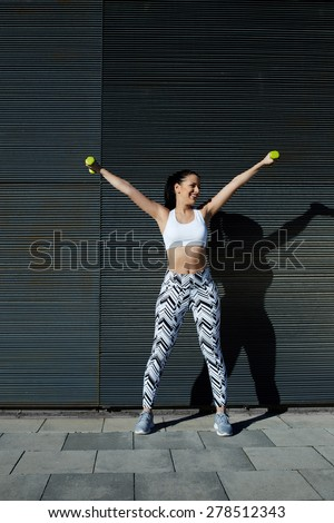 Smiling female with perfect figure getting her arms in great shape while lifting weights, attractive young woman using dumbbells to work out her arms while training outdoors on copy space background - stock photo