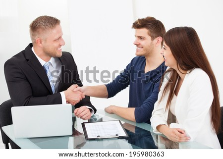 Smiling financial advisor shaking hand with couple at office desk - stock photo