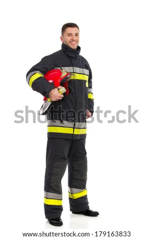 Smiling firefighter posing and holding red helmet under his arm. Full length studio shot isolated on white. - stock photo