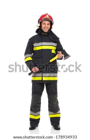 Smiling fireman holding axe. Full length studio shot isolated on white. - stock photo