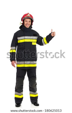 Smiling fireman showing thumb up and looking at camera. Full length studio shot isolated on white. - stock photo
