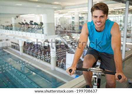 Smiling fit man on the spin bike at the gym - stock photo