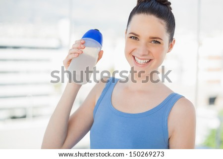 Smiling fit woman holding plastic flask after exercising in bright sports hall - stock photo