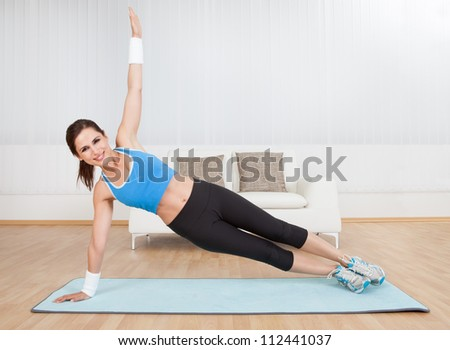 Smiling fit woman practising yoga balancing on one arm with her body raised off the floor in a health and fitness concept - stock photo