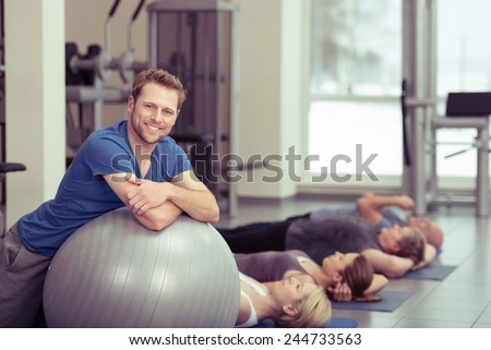 Smiling Fit Young Man Leaning on Gray Large Exercise Ball with Women at the Back Exercising. Captured Inside the Fitness Gym. - stock photo