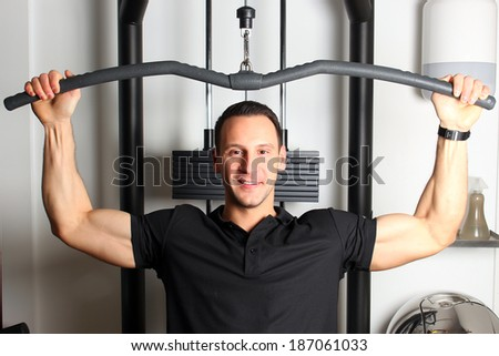 Smiling fitness guy working out in gym toning upper part of his body. - stock photo