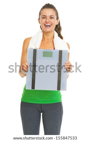 Smiling fitness young woman showing scales - stock photo