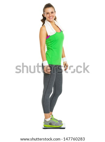 Smiling fitness young woman standing on scales - stock photo