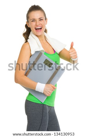 Smiling fitness young woman with scales showing thumbs up - stock photo