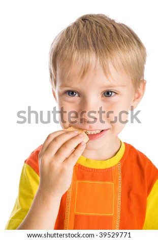 smiling five-year-old boy eating cookie isolated on white - stock photo