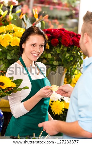 Smiling florist man customer buying flowers credit card shop - stock photo