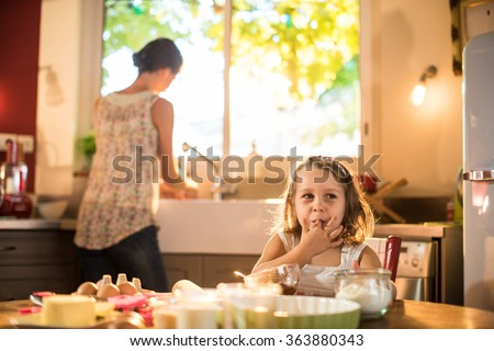 Smiling four years old blonde girl sitting at the kitchen table, licking melted chocolate on her fingers. Her mother is doing the dishes in the blurred background. They are cooking a tart. - stock photo