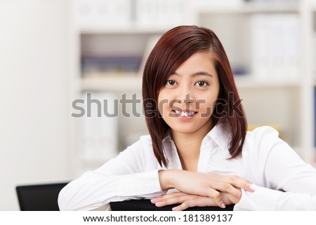 Smiling friendly Asian businesswoman or student sitting leaning on the back of the chair looking at the camera - stock photo