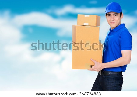 Smiling friendly delivery man carrying parcel boxes on blur blue sky background - stock photo