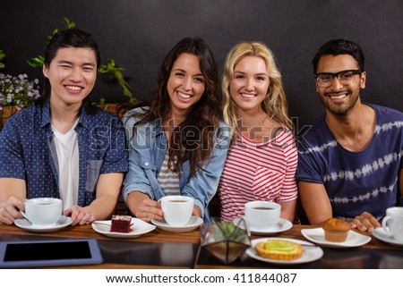Smiling friends enjoying coffee together and using technologies at the coffee shop - stock photo