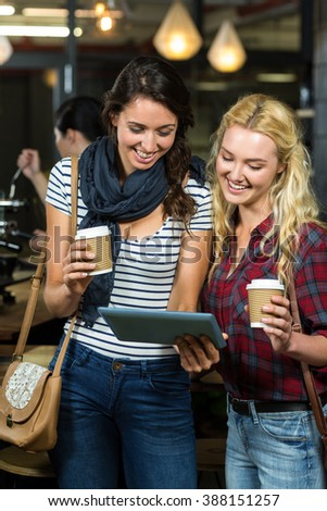 Smiling friends enjoying coffee while using tablet at the coffee shop - stock photo