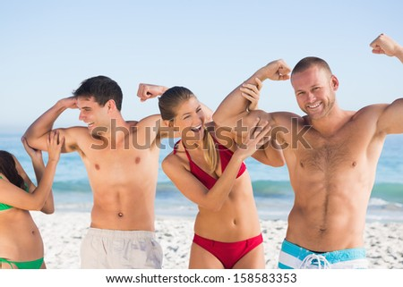 Smiling friends having fun together on the beach - stock photo