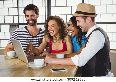 Smiling friends looking at laptop and having coffee at coffee shop - stock photo