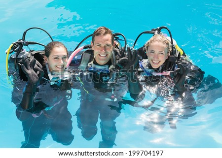 Smiling friends on scuba training in swimming pool looking at camera on a sunny day - stock photo