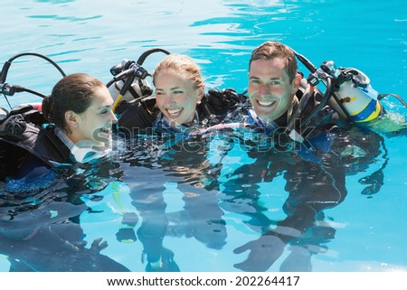 Smiling friends on scuba training in swimming pool on a sunny day - stock photo