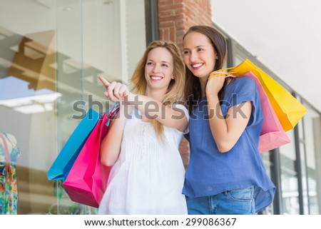 Smiling friends pointing away while holding shopping bags - stock photo