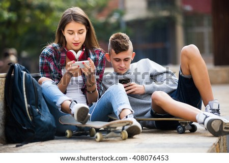 Smiling friends relaxing with mobile phones in sunny day  - stock photo