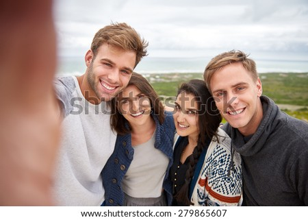 Smiling friends taking a group selfie while on a nature hike outdoors - stock photo
