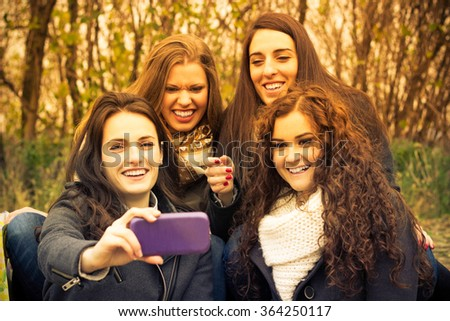 Smiling friends taking selfie, enjoying the sunny autumn day, in the park  - stock photo