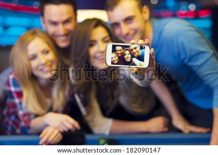Smiling friends taking selfie photo from nightclub with billiard - stock photo