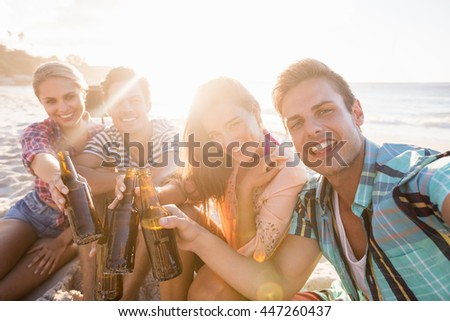 Smiling friends with beer at the beach - stock photo