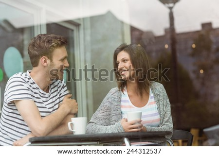 Smiling friends with mug of coffee in cafe at the university - stock photo