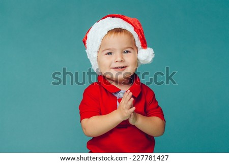 Smiling funny child (kid, boy) in Santa red hat.  Christmas concept. Shooting on blue background - stock photo